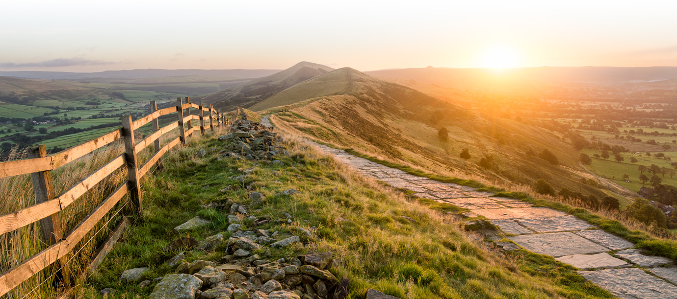 hilly terrain with fence at sunset