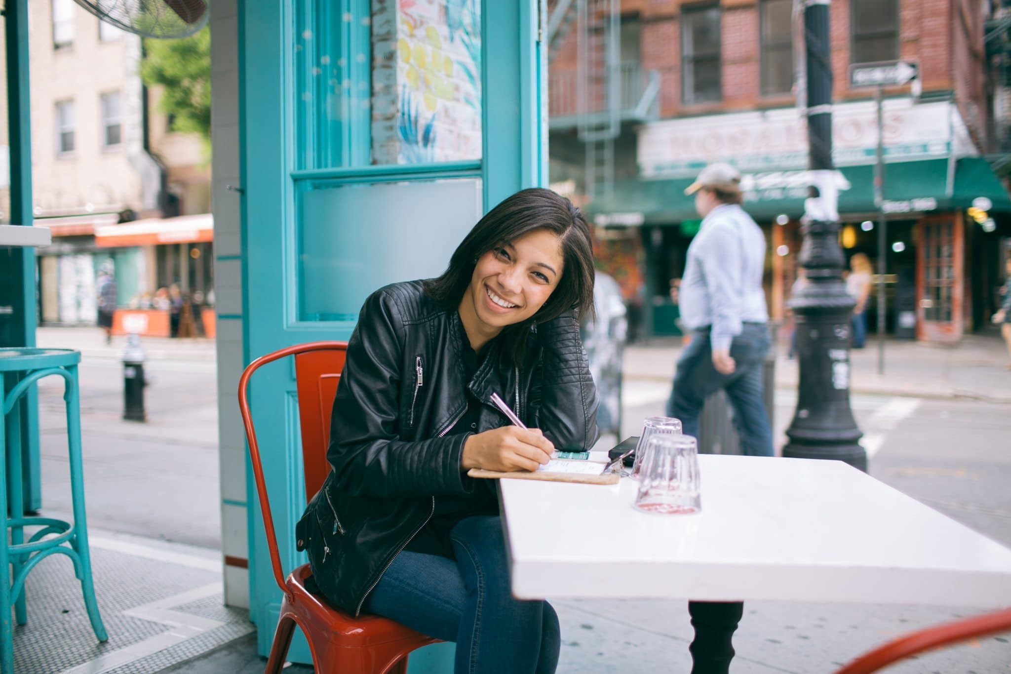 girl with notebook sitting at street cafe table