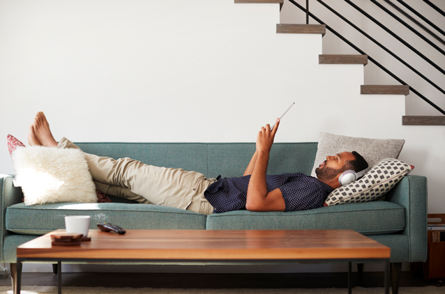 man looking at iPad on green couch