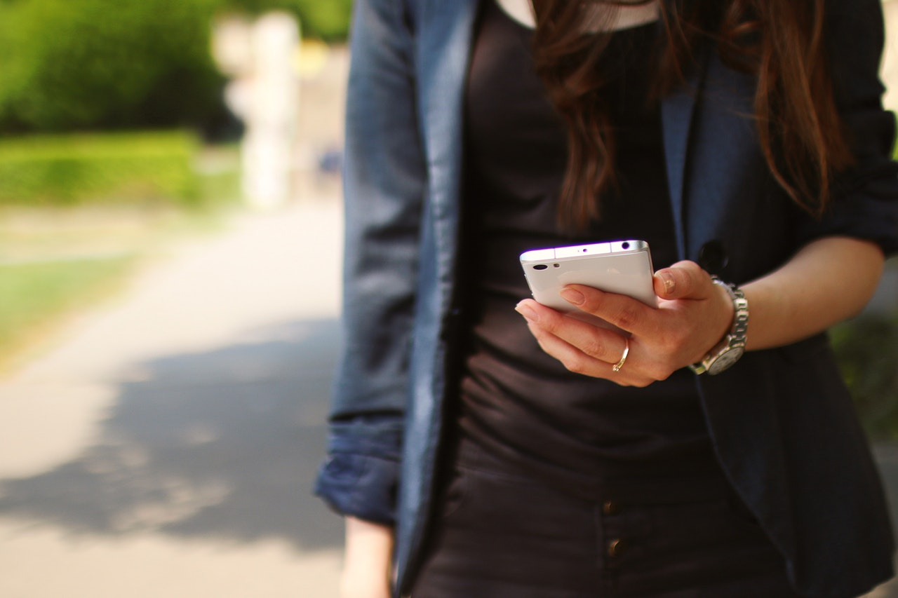 girl texting outside wearing blue jacket