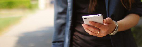 girl texting outside wearing blue jacket